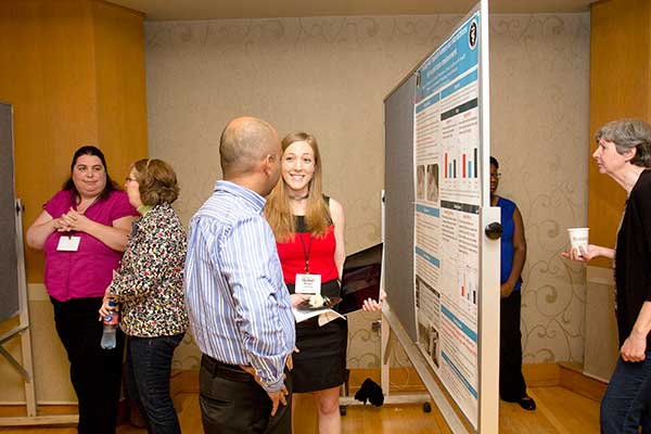 Graduate students and CAWS members Megan LaFollette (center) and Amy Robinson-Junker (left) discuss their posters with Symposium attendees.