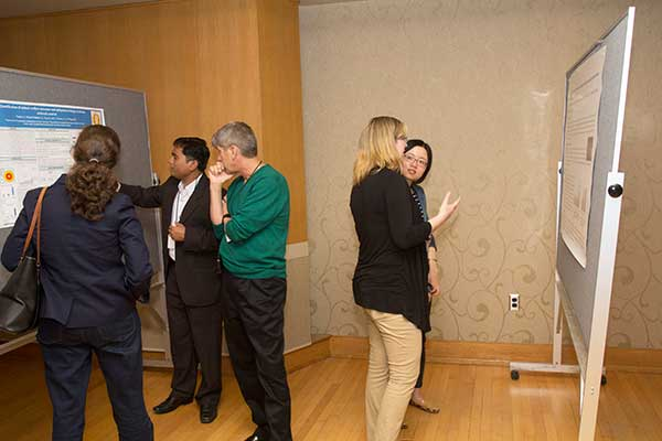 CPB Graduate student Shankar (left) with Symposium attendees during poster session.